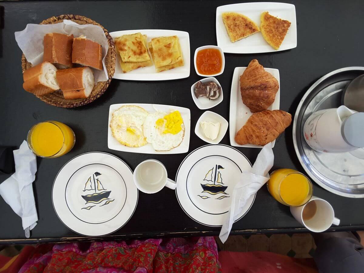 Tisch mit Tellern, Croissanst, Pfannkuchen, Brot, Butter, Marmelade, Orangensaft und Kaffee.