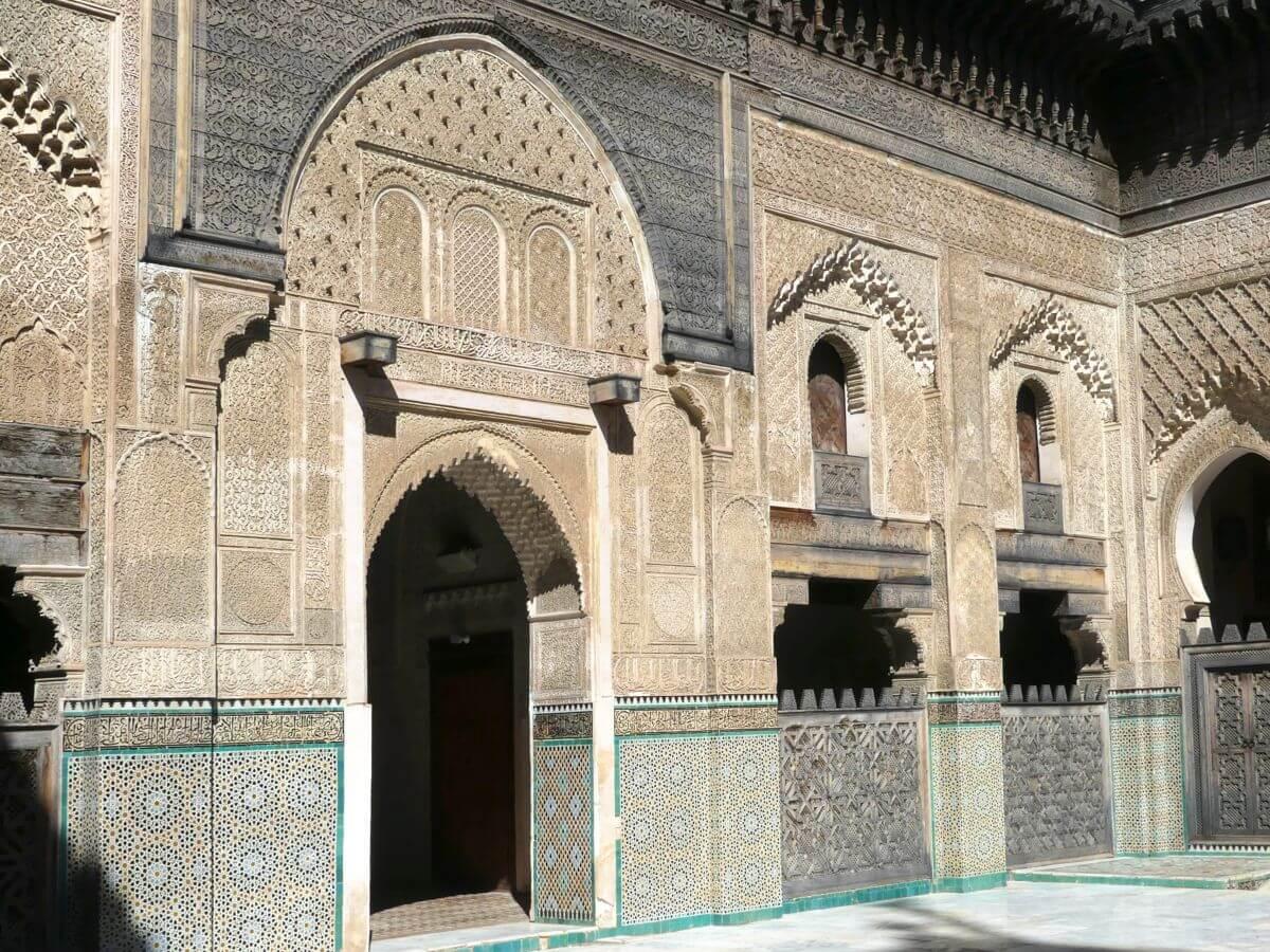 orientalische Torbögen, helle Wände mit Stuckverzierungen in der Medersa.