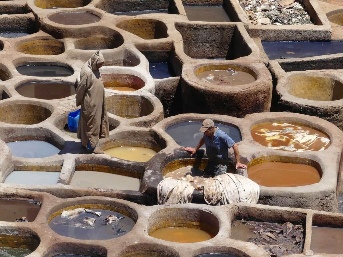 Viele Becken mit verschiedenfarbigen Flüssigkeiten gefüllt, ein Arbeiter, der die Häute bearbeitet und ein Aufseher in den Gerbereien von Fes.