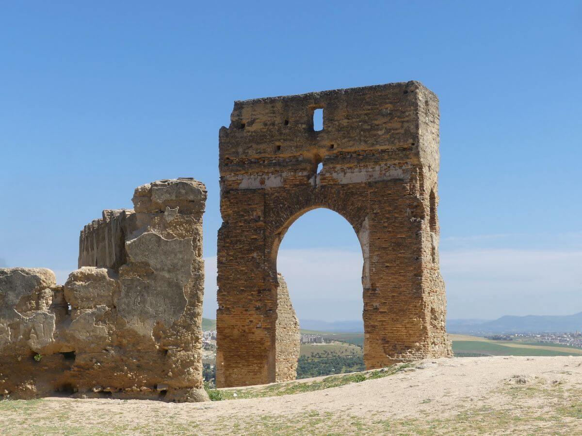Reste eines Torbogens auf einem Hügel, dahinter Blick über die Landschaft.