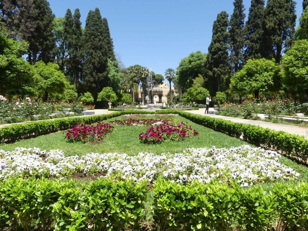 Symmetrische Parkanlage mit Rasen und blühenden Sträuchern.