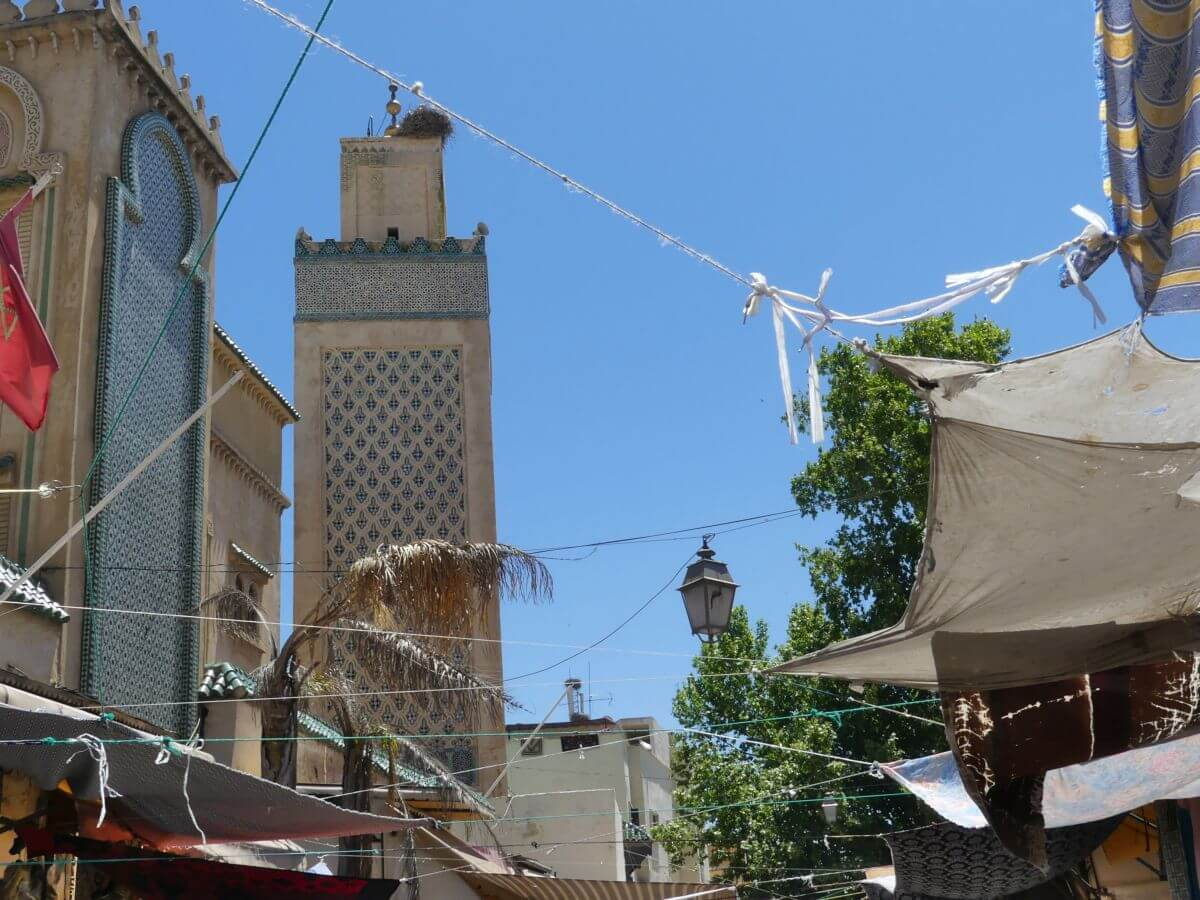 Moschee-Turm mit grünen Verzierungen ragt zwischen den Gassen von Fes hervor.