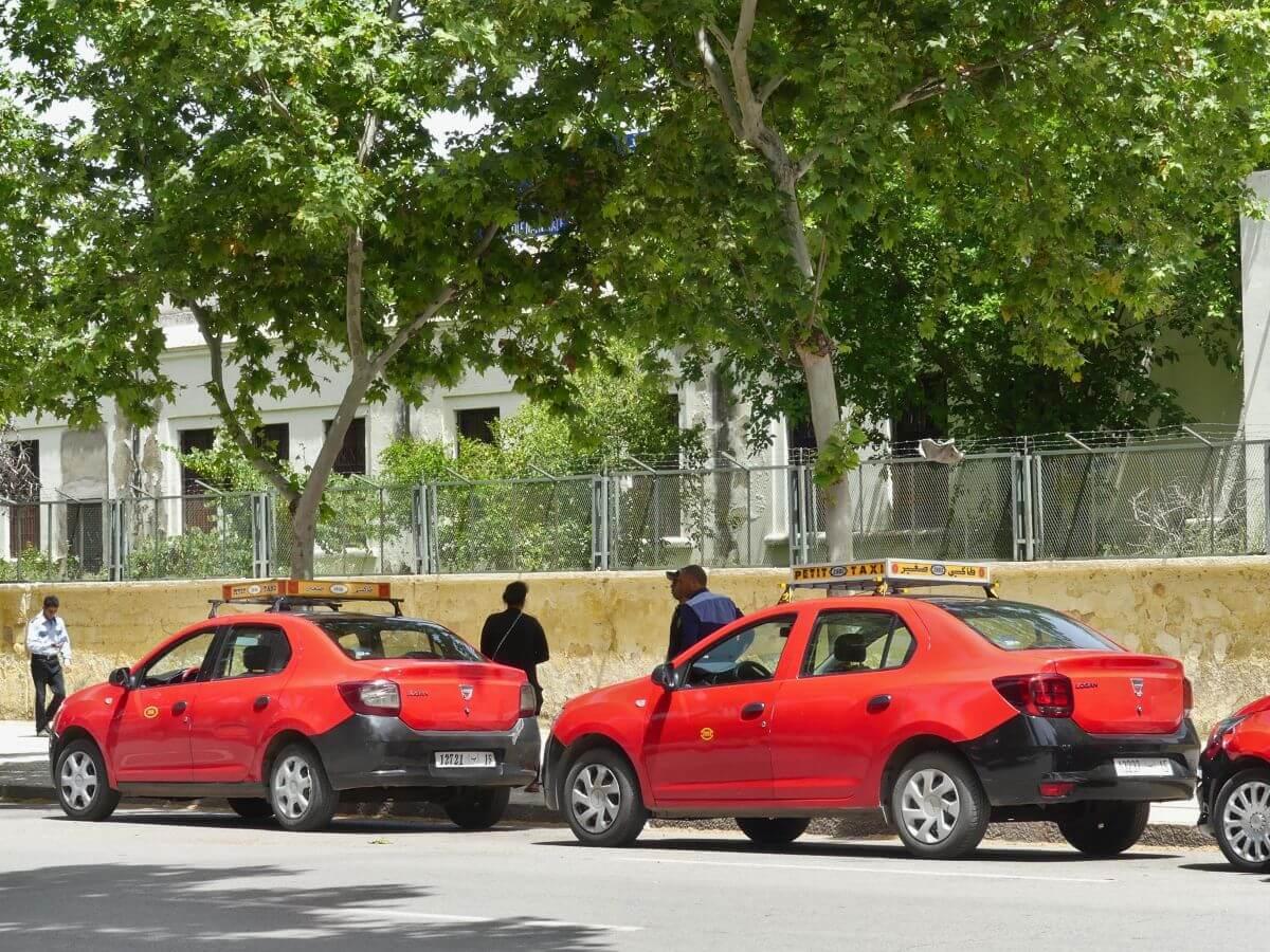 Zwei rote Taxis warten am Straßenrand.