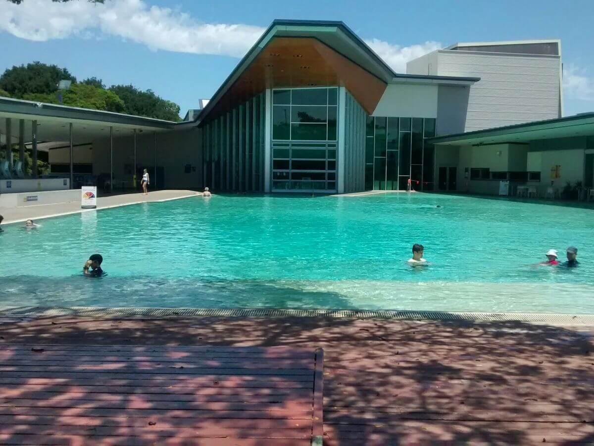 Türkisfarbener großer Pool vor modernem Gebäude