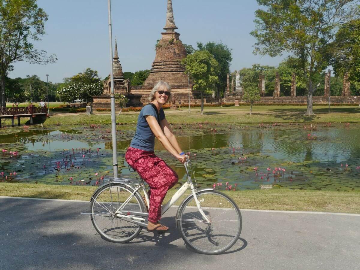 Gina auf Fahrrad vor buddhistischem Tempel