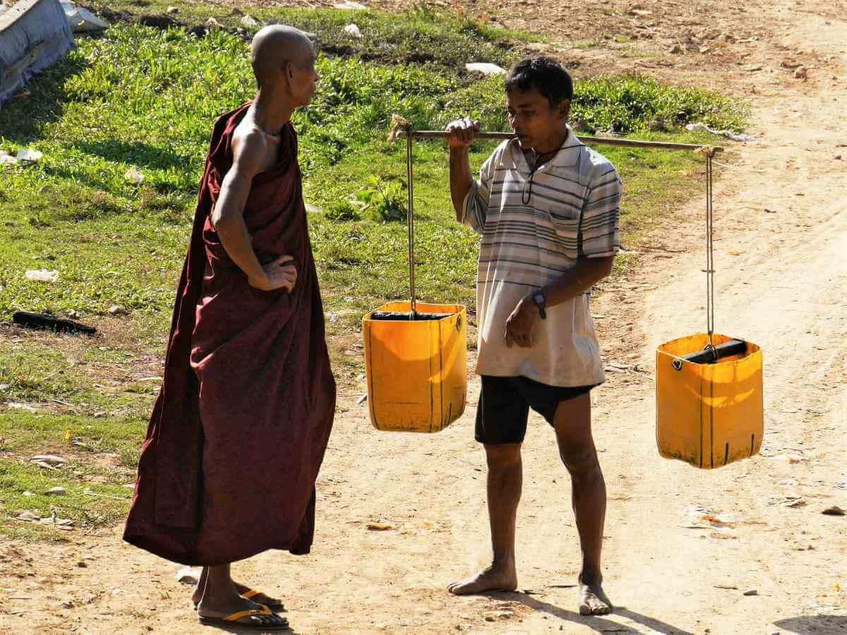 Buddhistischer Mönch unterhält sich mit einem Wasserträger.