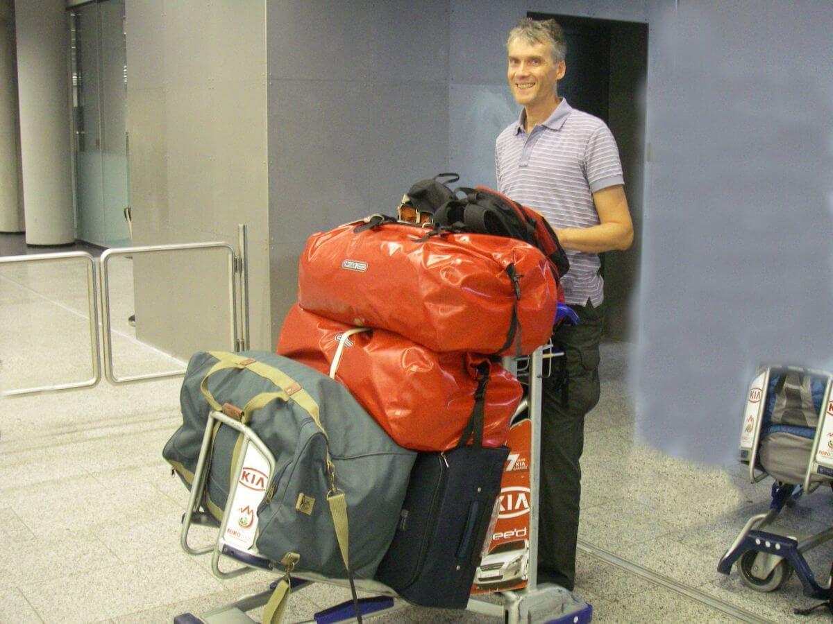 Marcus schiebt einen Gepäckwagen mit vier großen Reisetaschen.