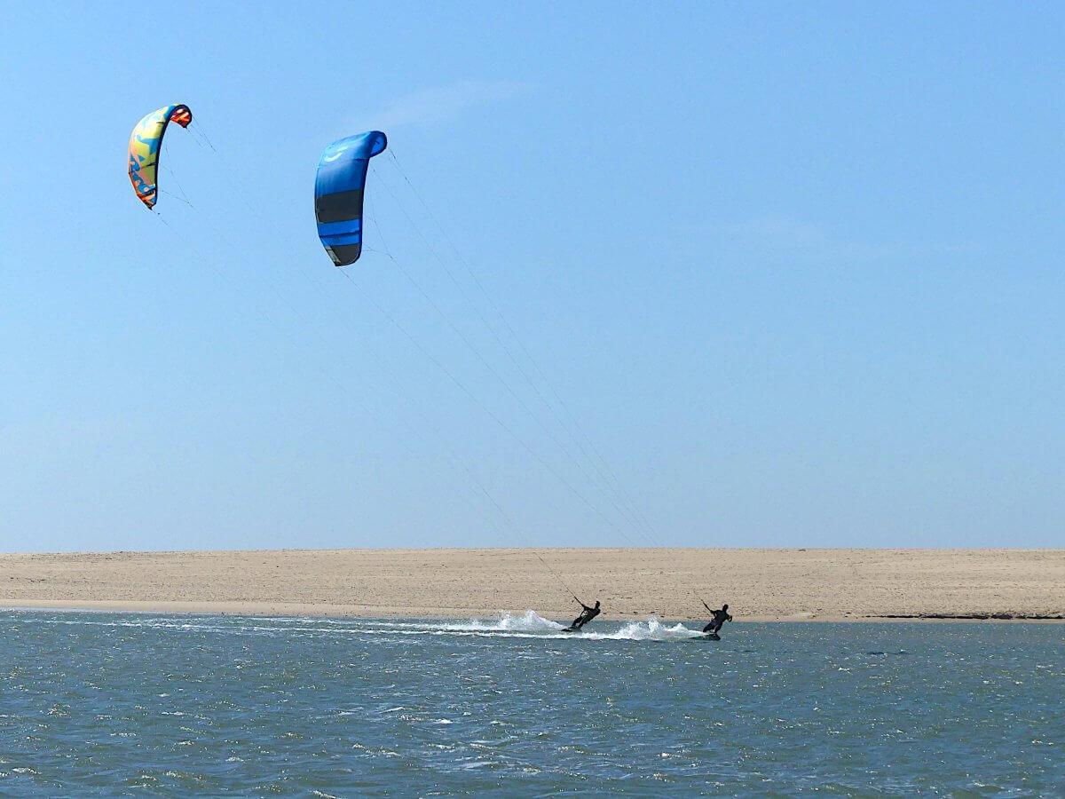 Zwei Kitesrufer flitzen über das Wasser der Lagune von Obidos, dahinter Sandstrand.
