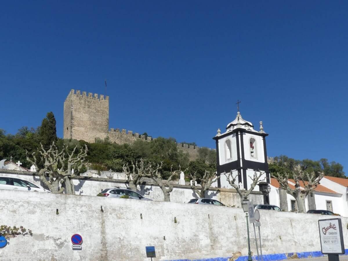 REchteckiger Turm der Stadtmauer, im Vordergrund eine Kirche.