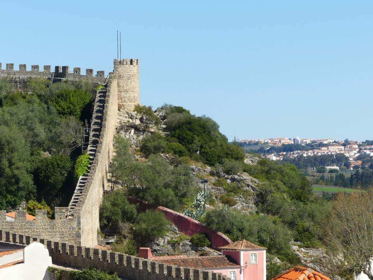Die Stadtmauer zieht sich einen Hügel empor, daneben grüne Landschaft.