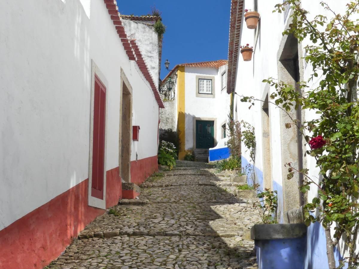 Gasse mit Kopfsteinpflaster, weißen Häusern und Blumen in Obidos.