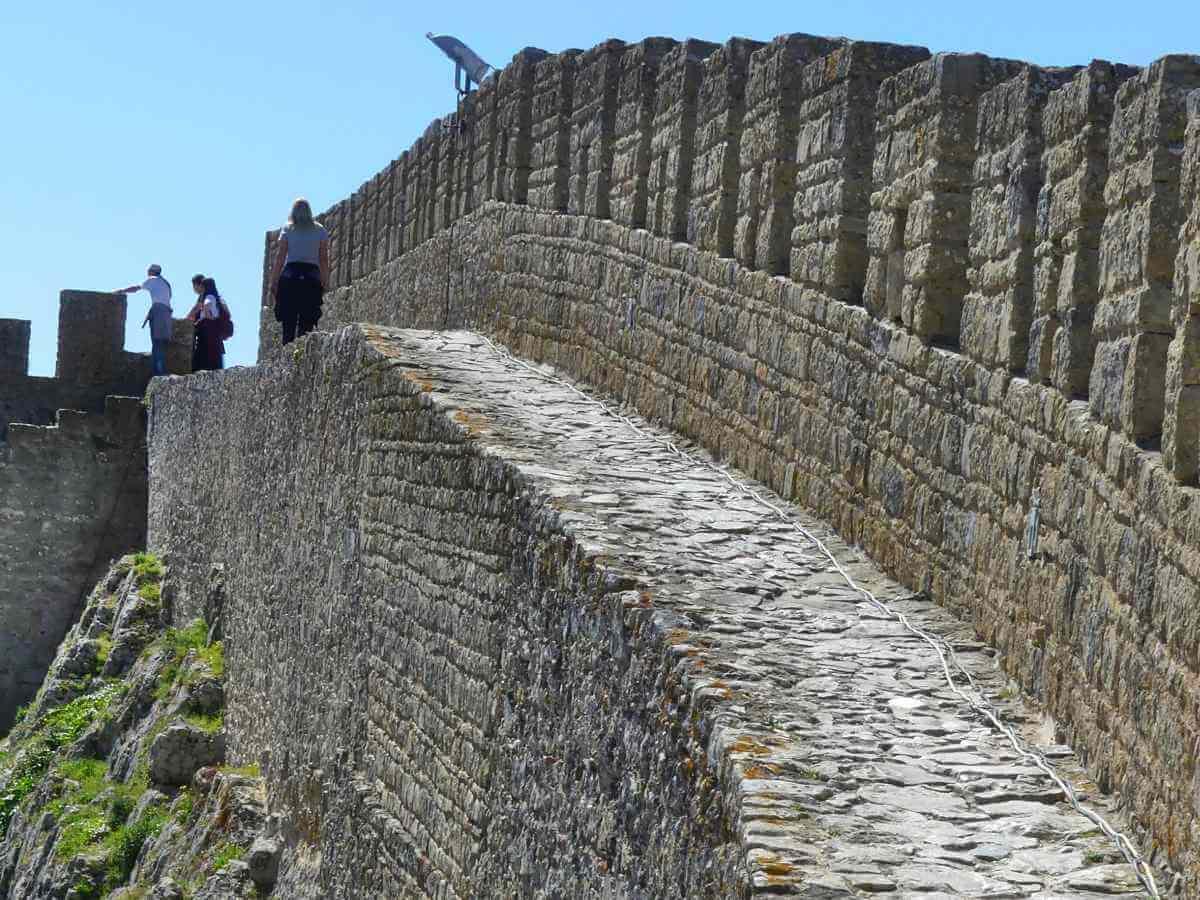 Steg mit Mauer an einer Seite und Abgrund an der anderen Seite.