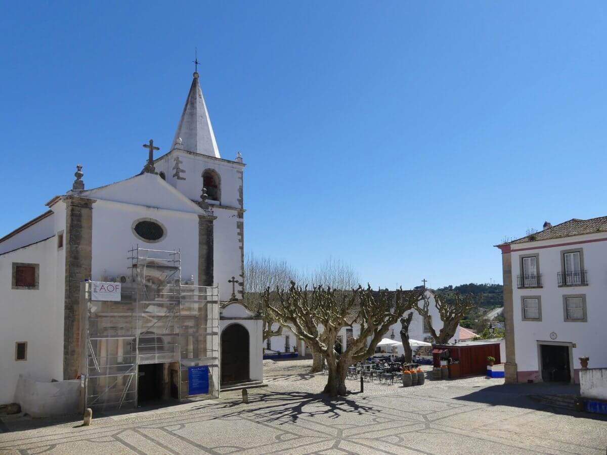 Weiße Kirche und Platz mit großem Baum in Obidos.