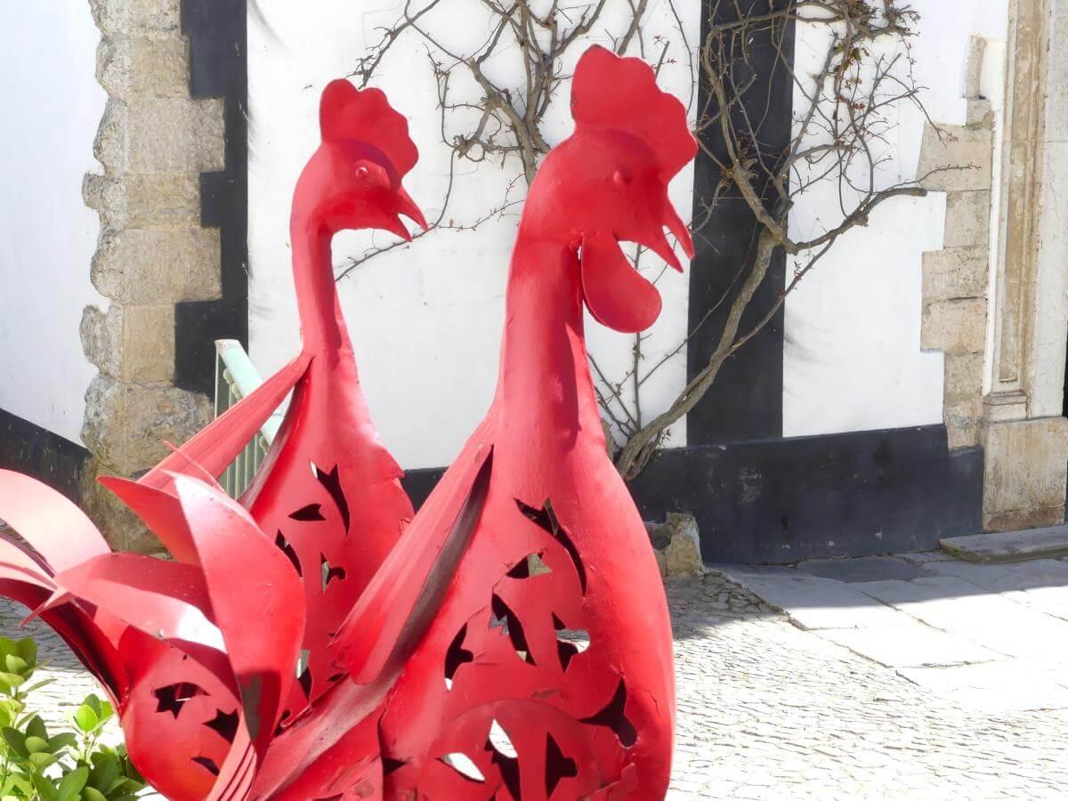 Zwei rote Hähne aus Blech.