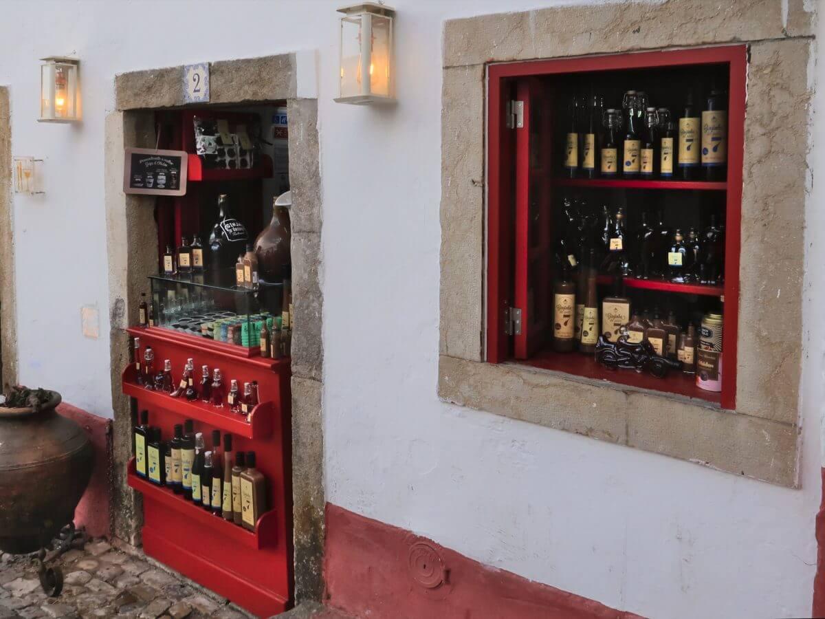 Fenster und Tür eines Ladens, in dem verschiedenen Ginja-Flaschen präsentiert werden.