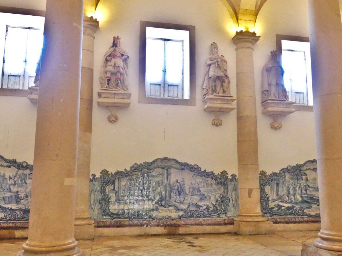 Saal mit Säulen, die Wände mit blauen Kachelbildern und Statuen geschmückt.