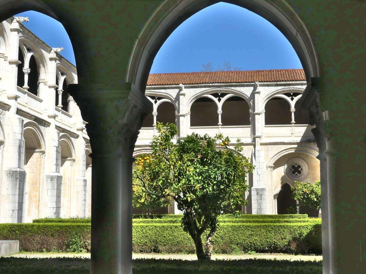Blick durch einen Bogen ins grüne Innere des Kreuzgangs in Alcobaca.