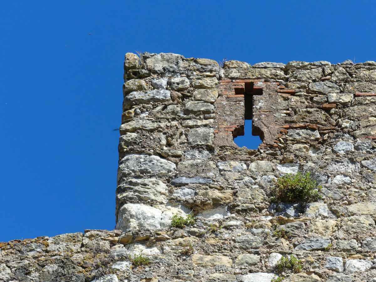 Graue Mauer mit Schießscharte in Kreuzform.
