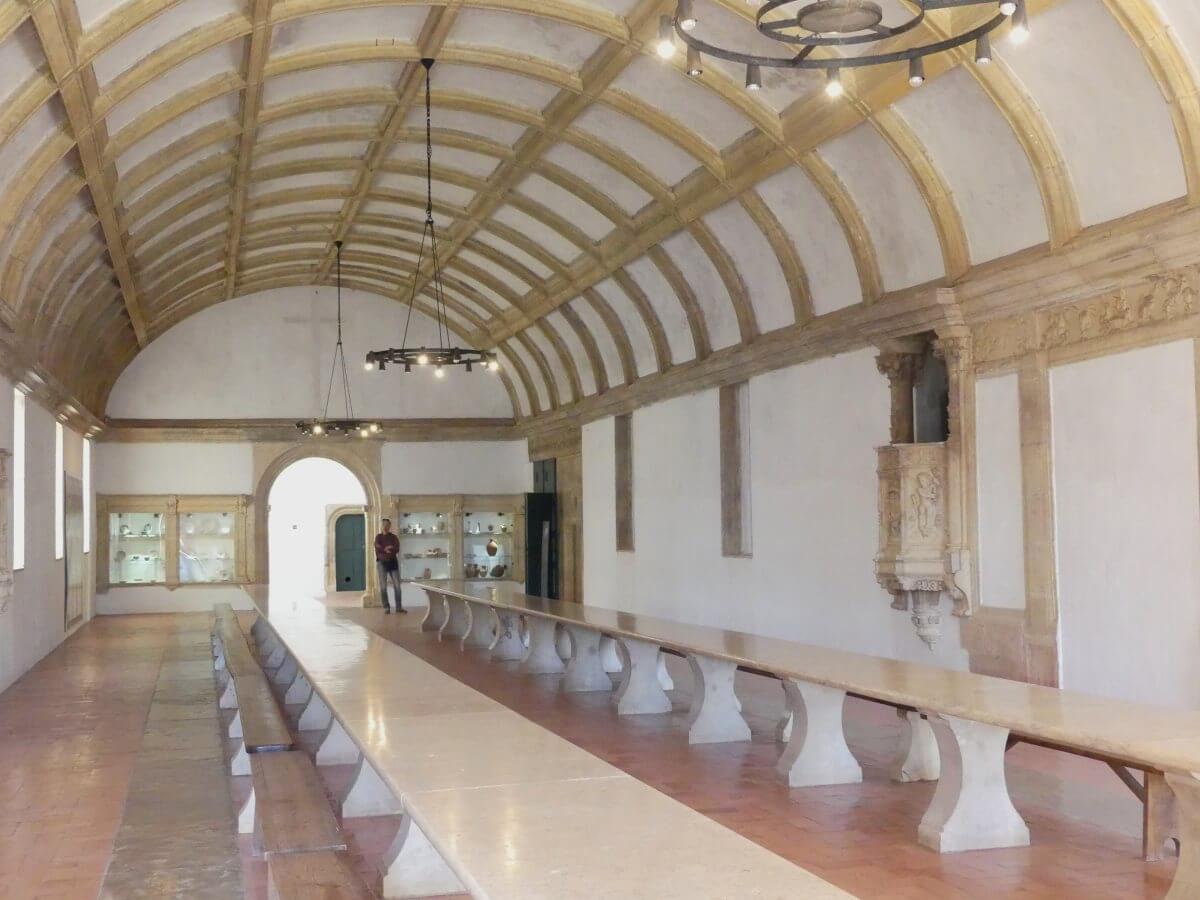 Großer Saal mit gewölbter Decke und langen Tischen.