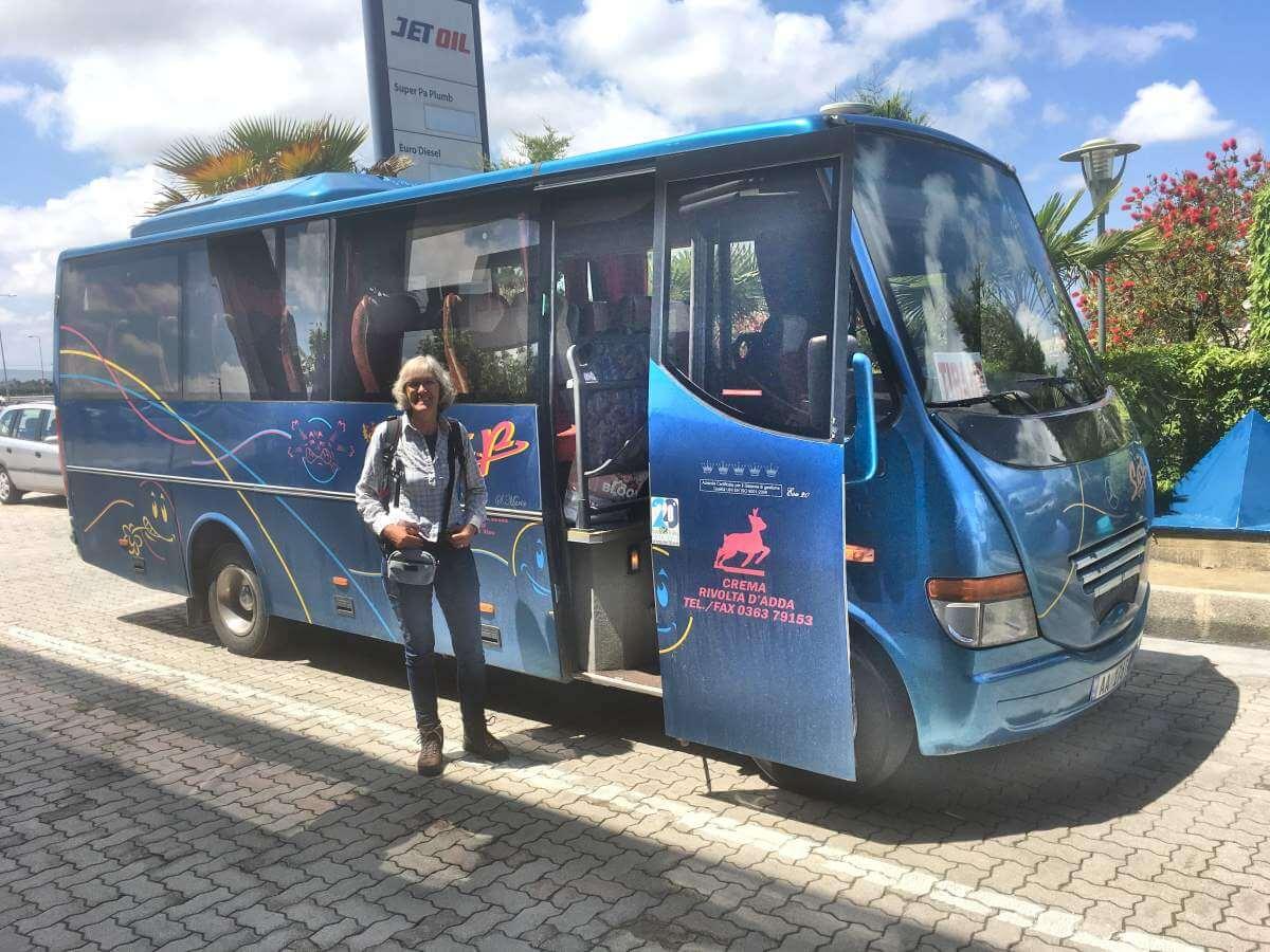 Gina steht vor einem blauen Bus.