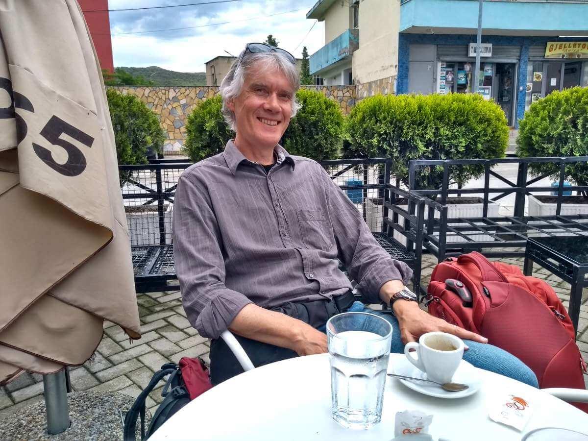 Marcus sitzt am Tisch mit einem Kaffee vor sich.