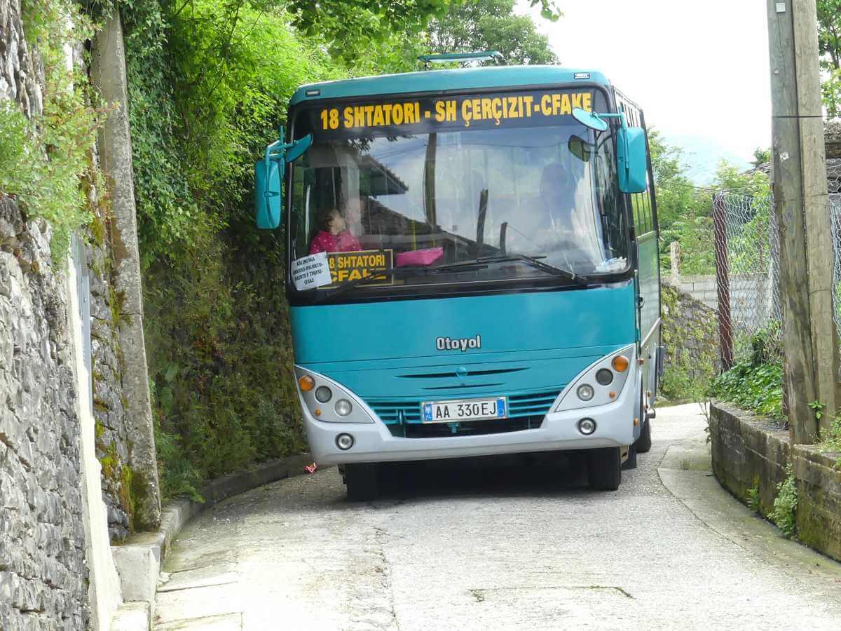 Blauer Minibus auf einer engen Straße mit Mauern rechts und links.
