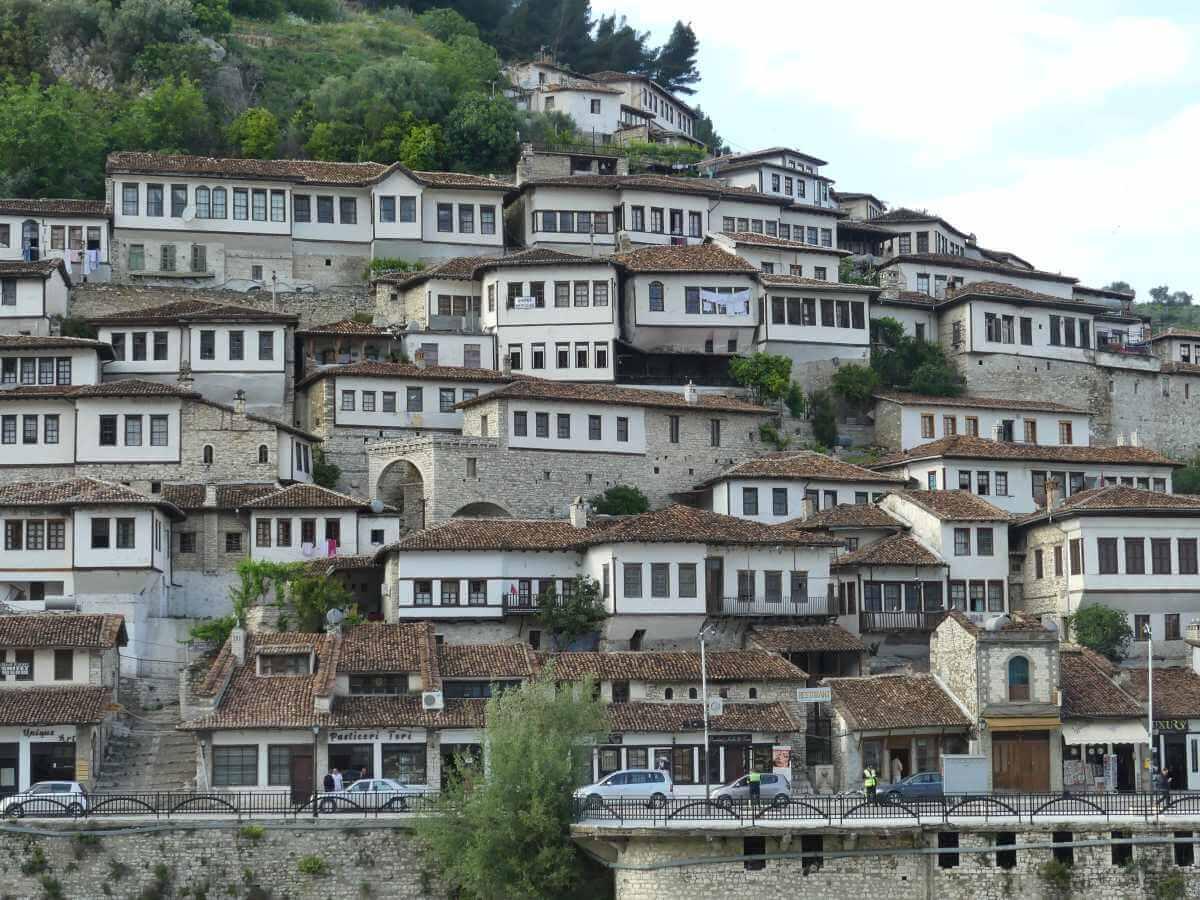 Viele Häuser in Berat mit Fensterreihen ziehen sich einen Hang entlang.