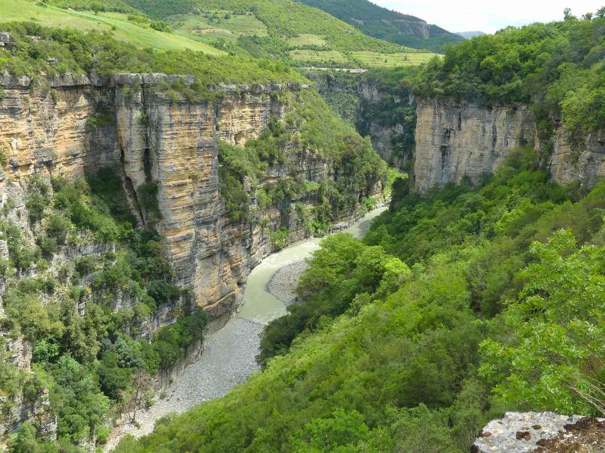 Canyon mit steilen Felswänden und einem Fluss am Grund.