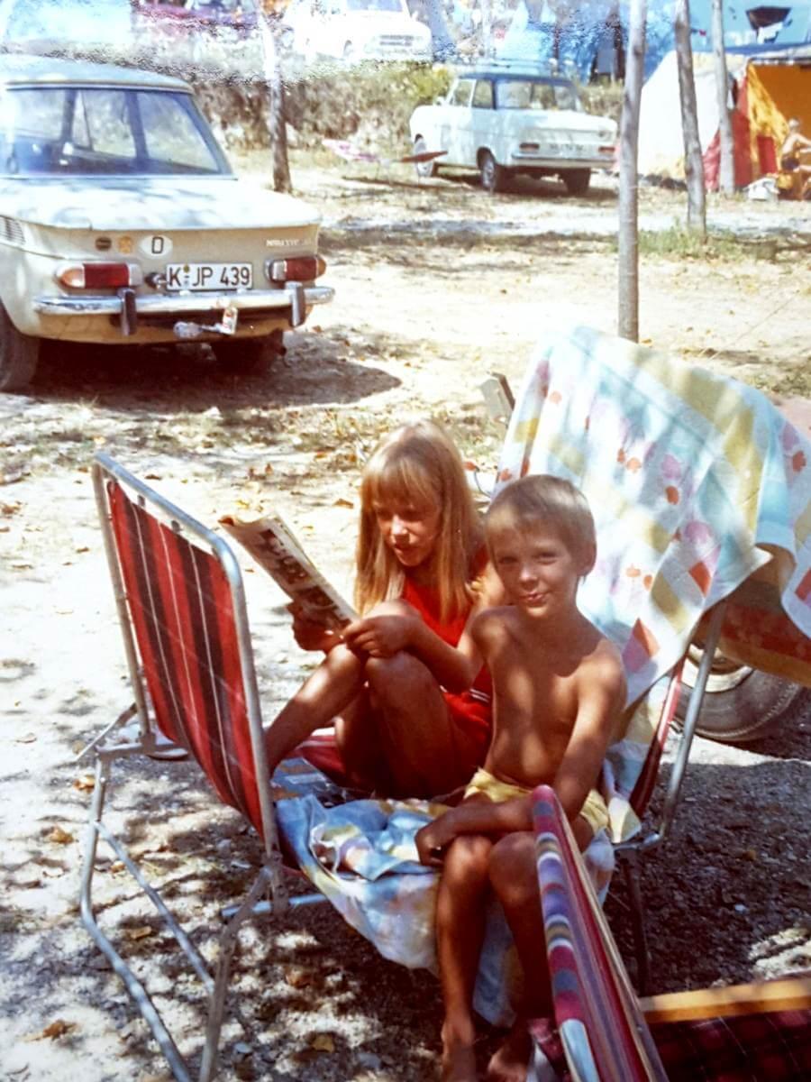 Zwei Kinder auf einem Liegstuhl, im Hintergrund das Auto.