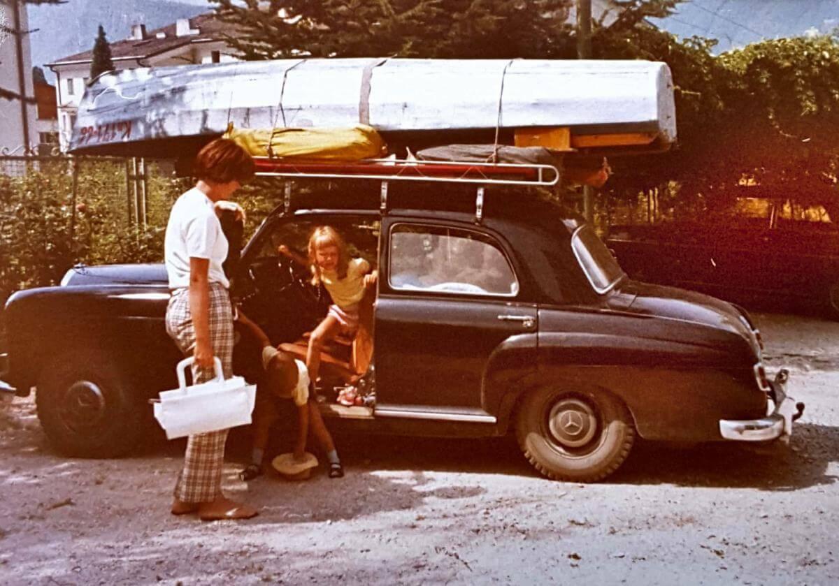 Alter schwarzer Mercedes mit Boot auf dem Dach.
