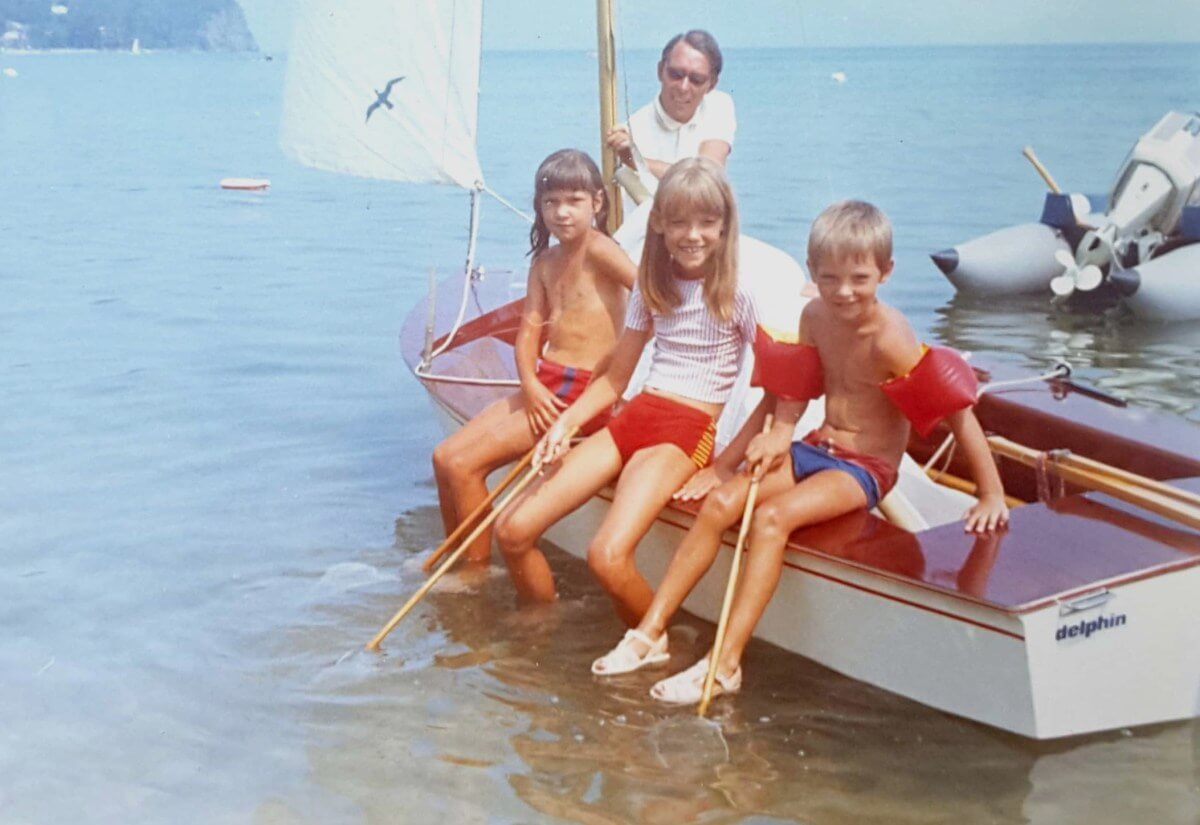 Drei Kinder sitzen auf dem Rand eines Segelboots.