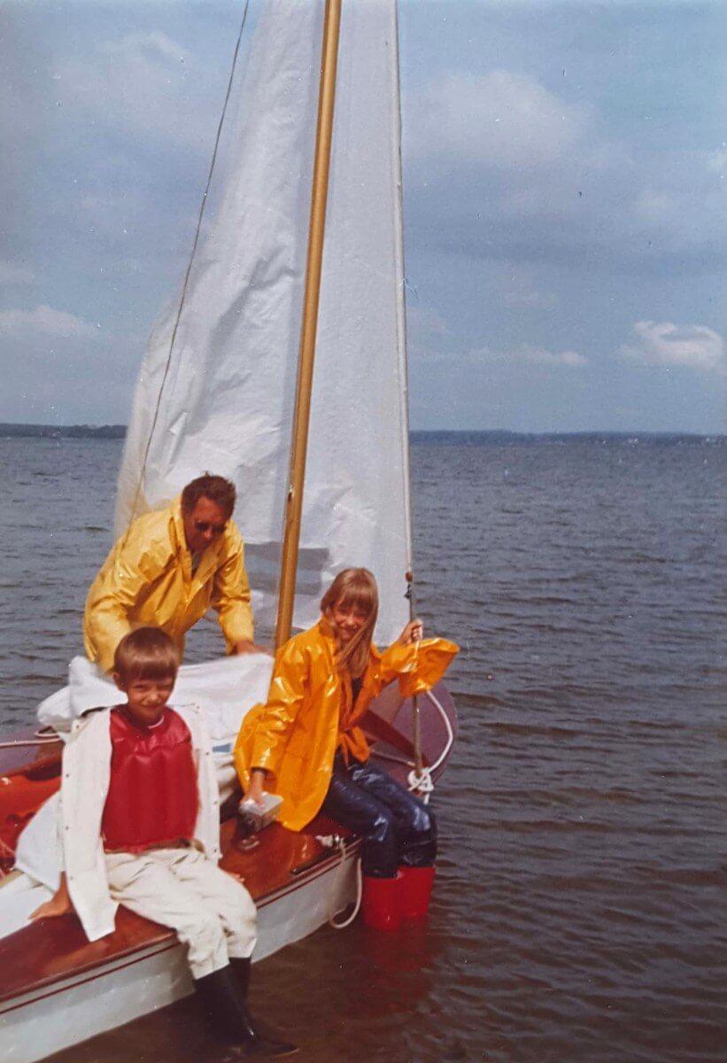 Kinder und Vater in Regenzeug auf dem Segelboot.