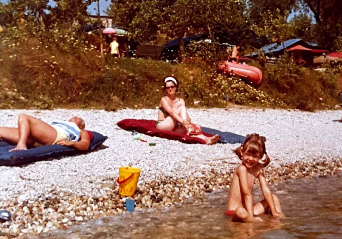 Mädchen sitzt im flachen Wasser am Kiesstrand.