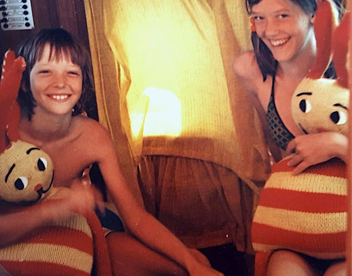 Zwei Kinder mit zwei rot-gelb geringelten Strickhasen.
