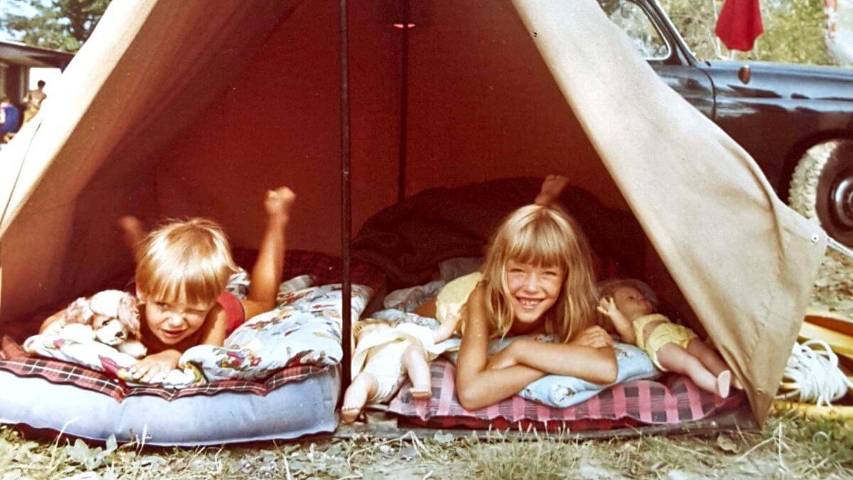 zwei Kinder liegen im offenen Zelt und schauen heraus.