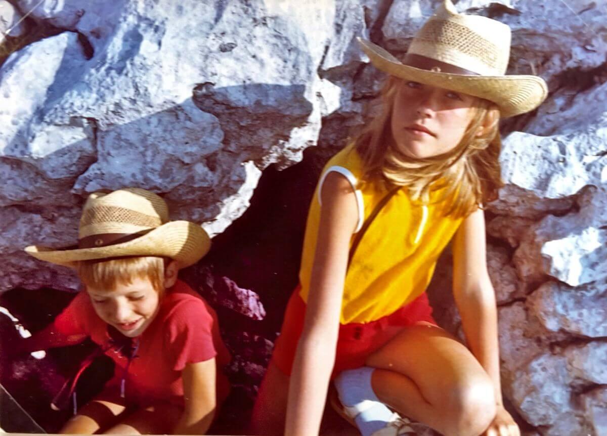 zwei Kinder mit Sonnenhüten kommen aus einer kleinen Höhle geklettert.