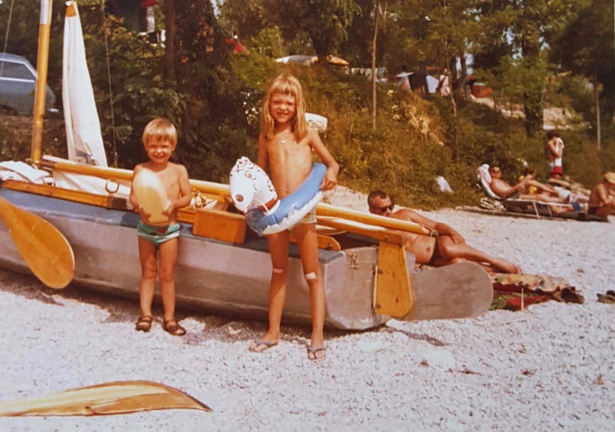 Zwei Kinder mit Schwimmringen stehen vor einem Boot am Strand.