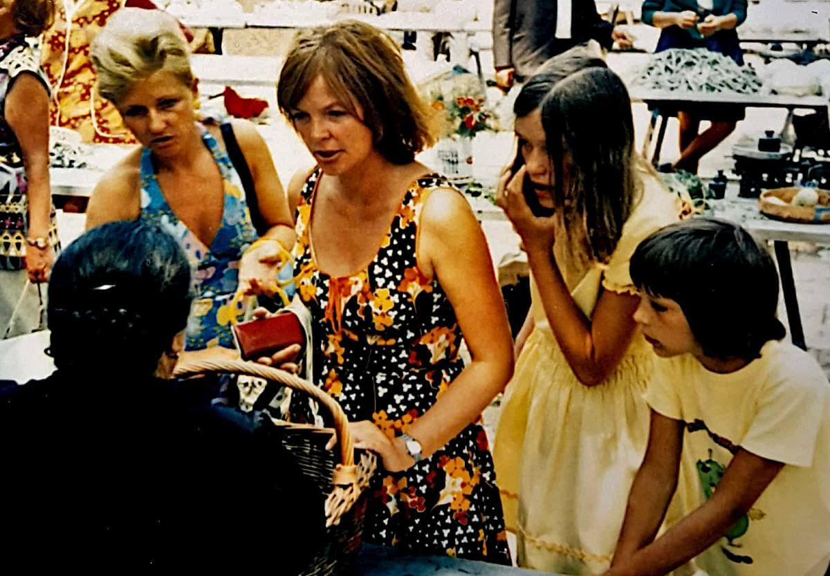 Zwei Frauen und zwei Kinder am Marktstand mit einer älteren Verkäuferin.