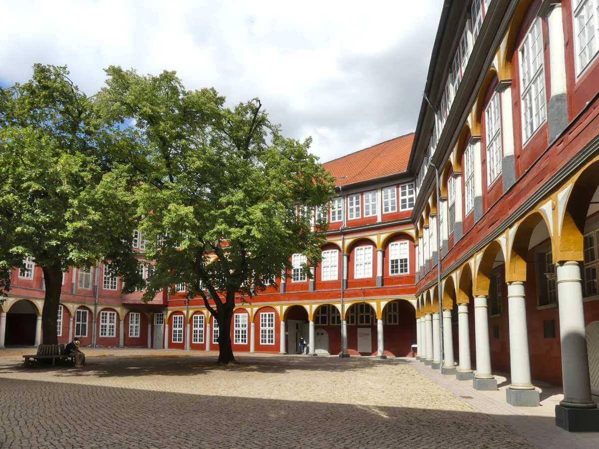 Hof mit weißen Säulengängen, roter Fassade und großem Baum.