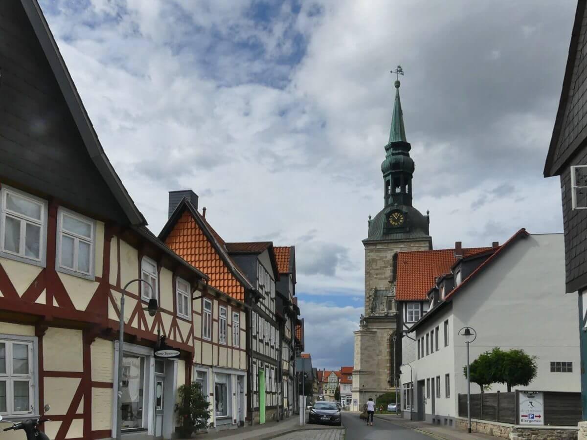 Blick durch Straße mit Fachwerkhäuseren auf die Kirche.
