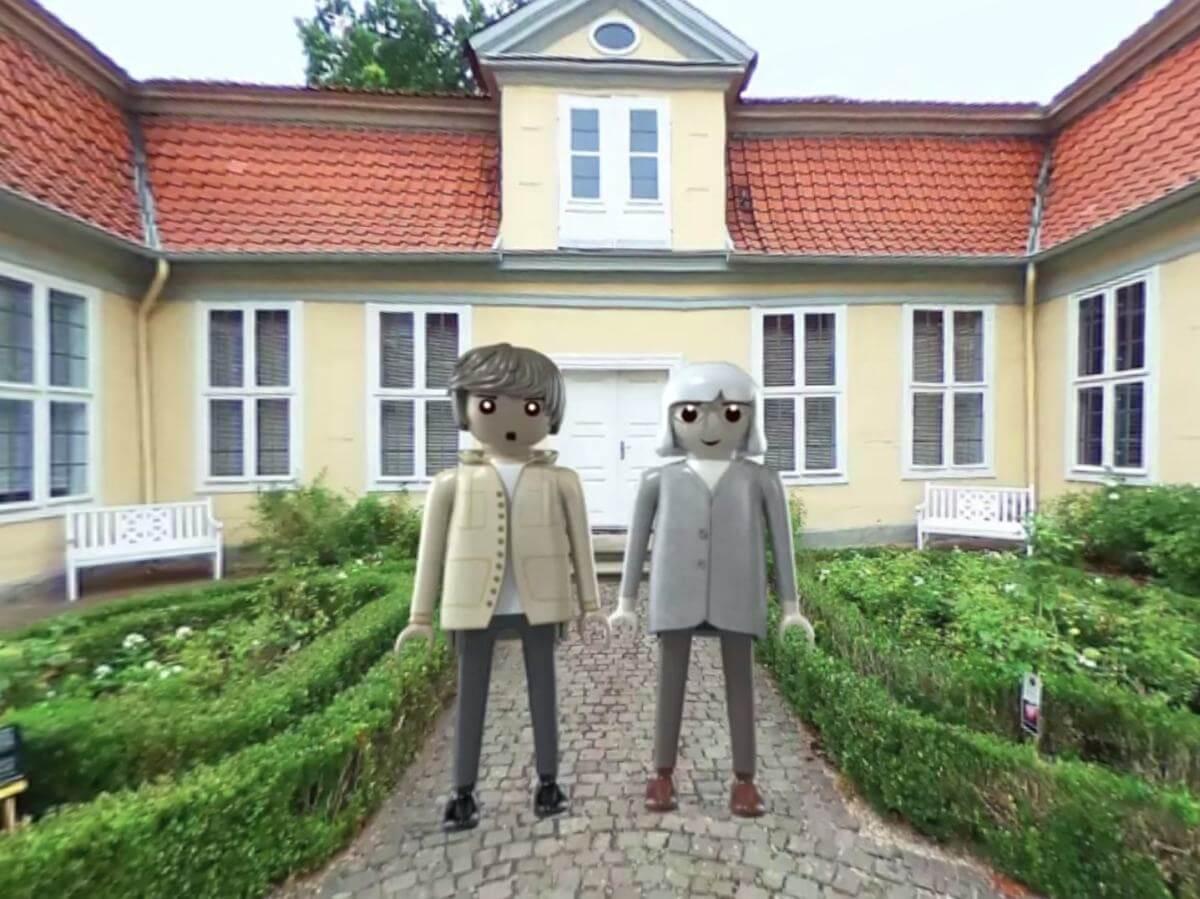 Zwei Playmobil-Figuren vor dem gelben Haus.