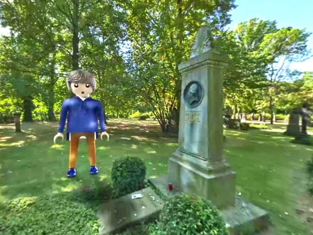 Playmobilfigur auf grünem Friedhof neben Grab.