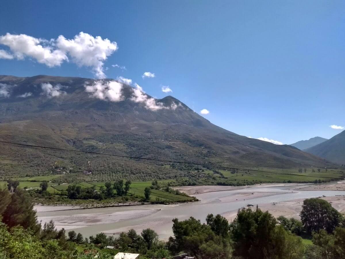 Berg an großem Fluss mit weißen Wolken um die Kuppe.