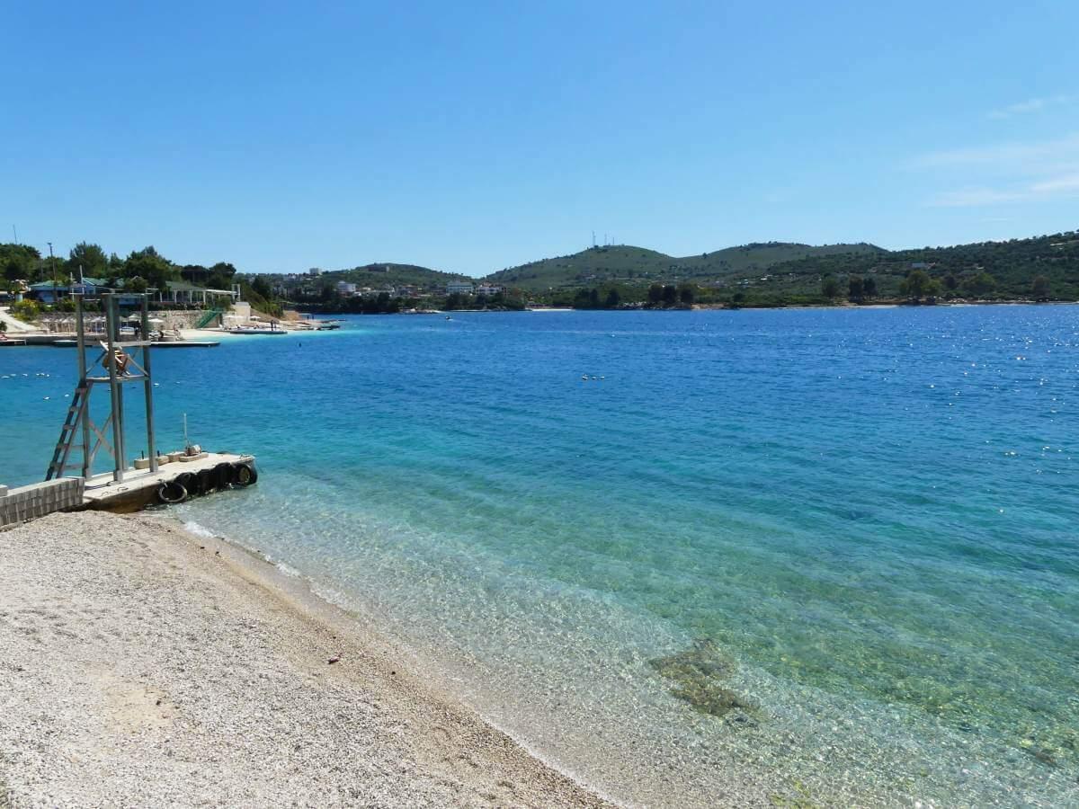 Strand mit kleinem Steg und blauem Meer.