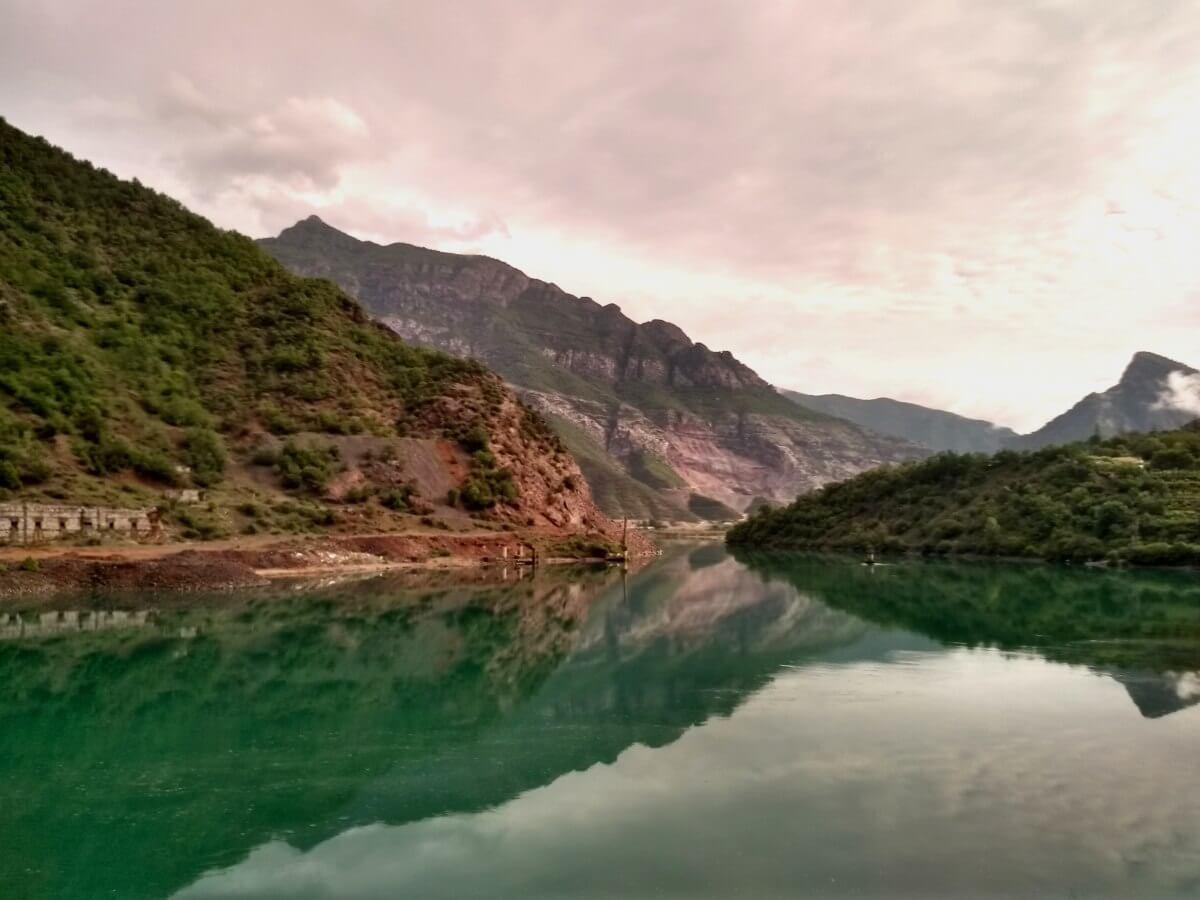 Berge und Wolken spiegeln sich in grünem See.