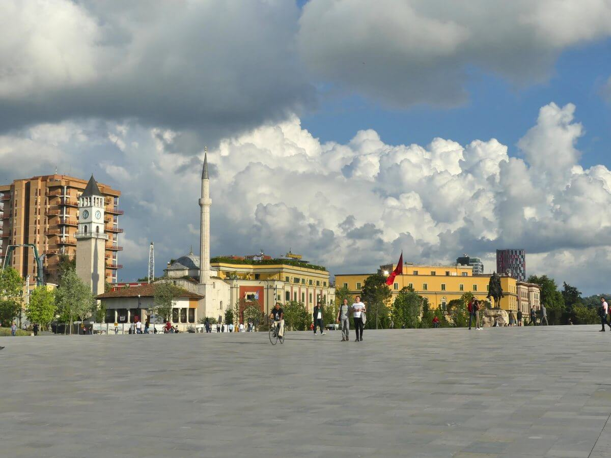 Großer Platz in Tirana mit Uhrturm und Minarett.