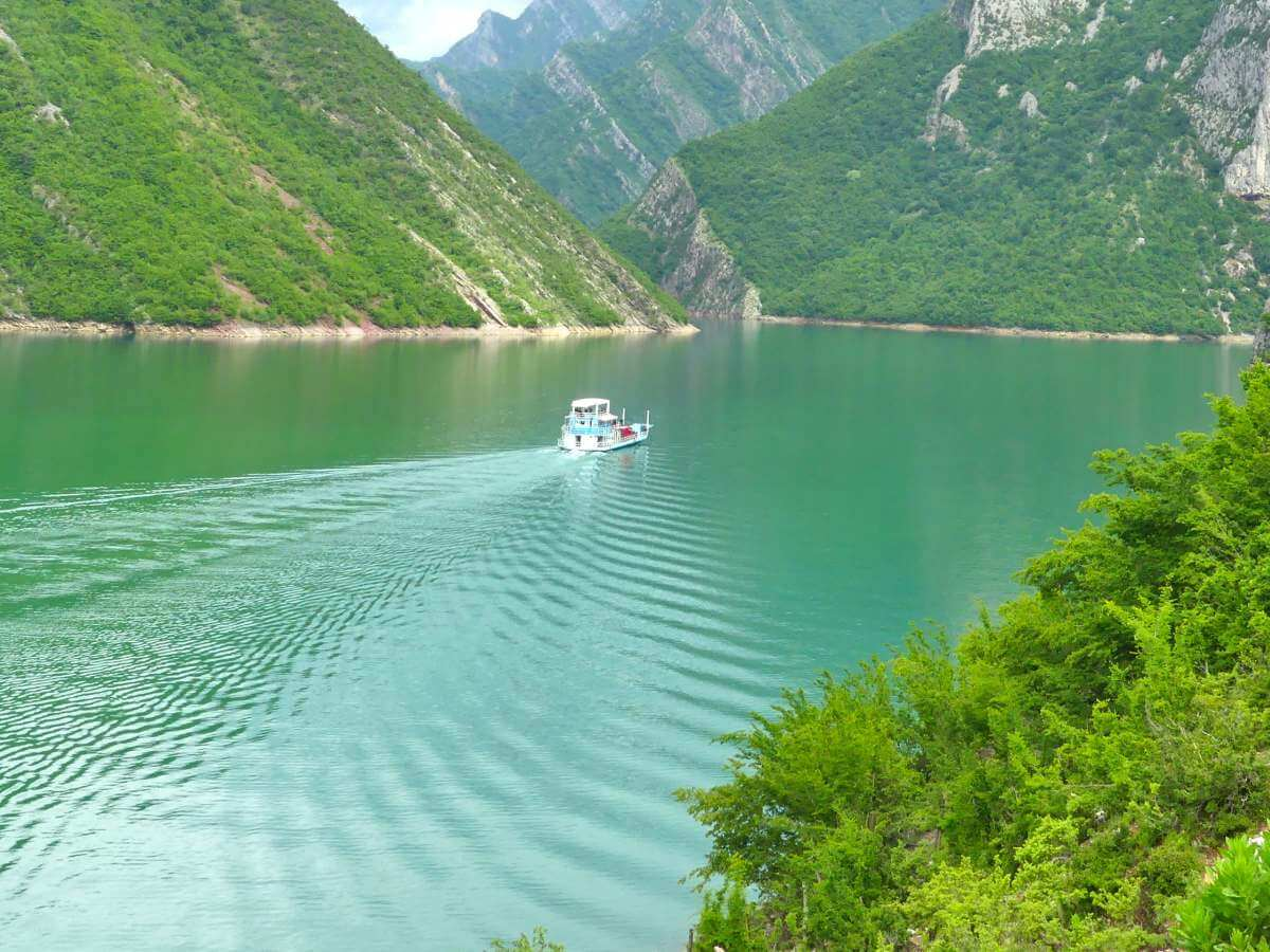 kleine Fähre fährt über smaragdgrünen See.