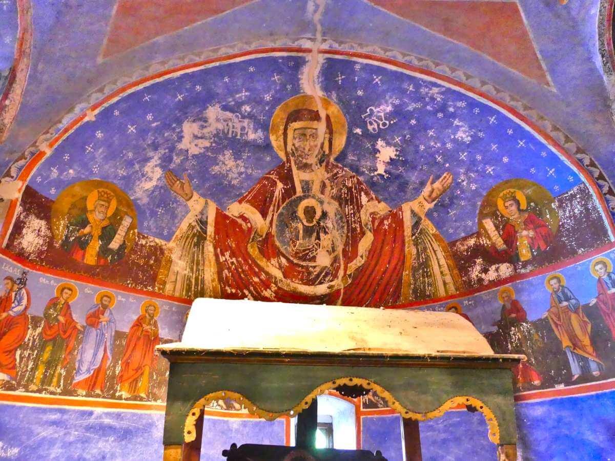 Apsis mit bunten Fresken.