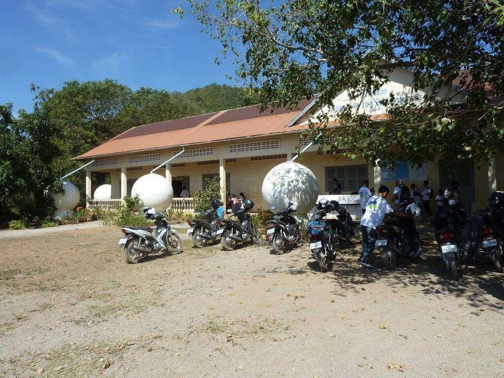 Einstöckiges Schulgebäude, davor kugelförmige Wassertanks.