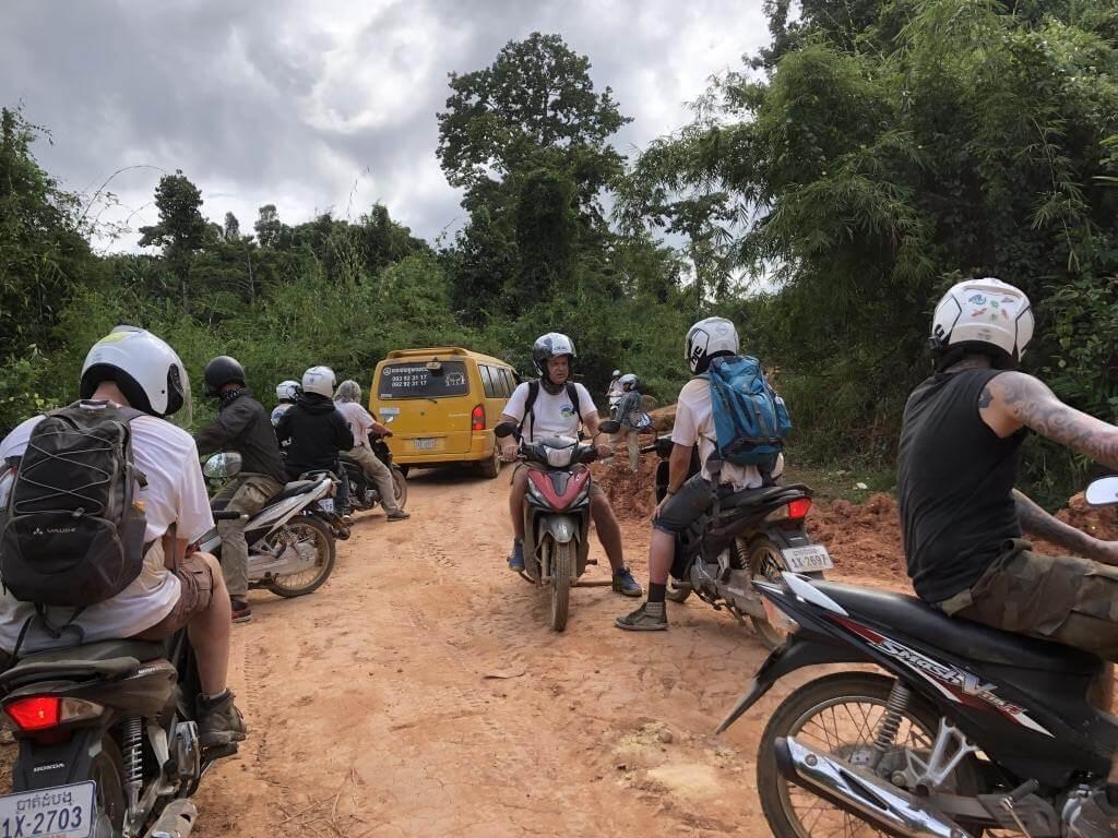Ein Van und eine Gruppe Rollerfahrer auf einer unbefestigten Straße.